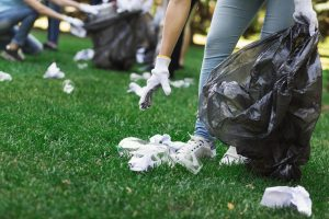 Young volunteers collecting garbage in suumer park